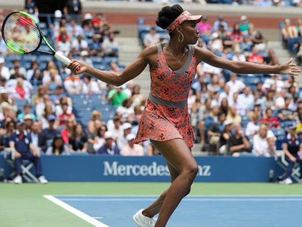 Venus Williams in oversize drop-hoop earrings and a coral, gray, and black abstract-pattern dress from her Eleven by Venus line