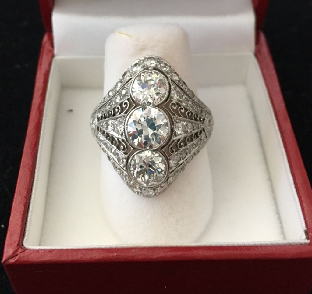 A three-stone diamond ring in a linear pattern with scrolls that Christine purchased for herself.