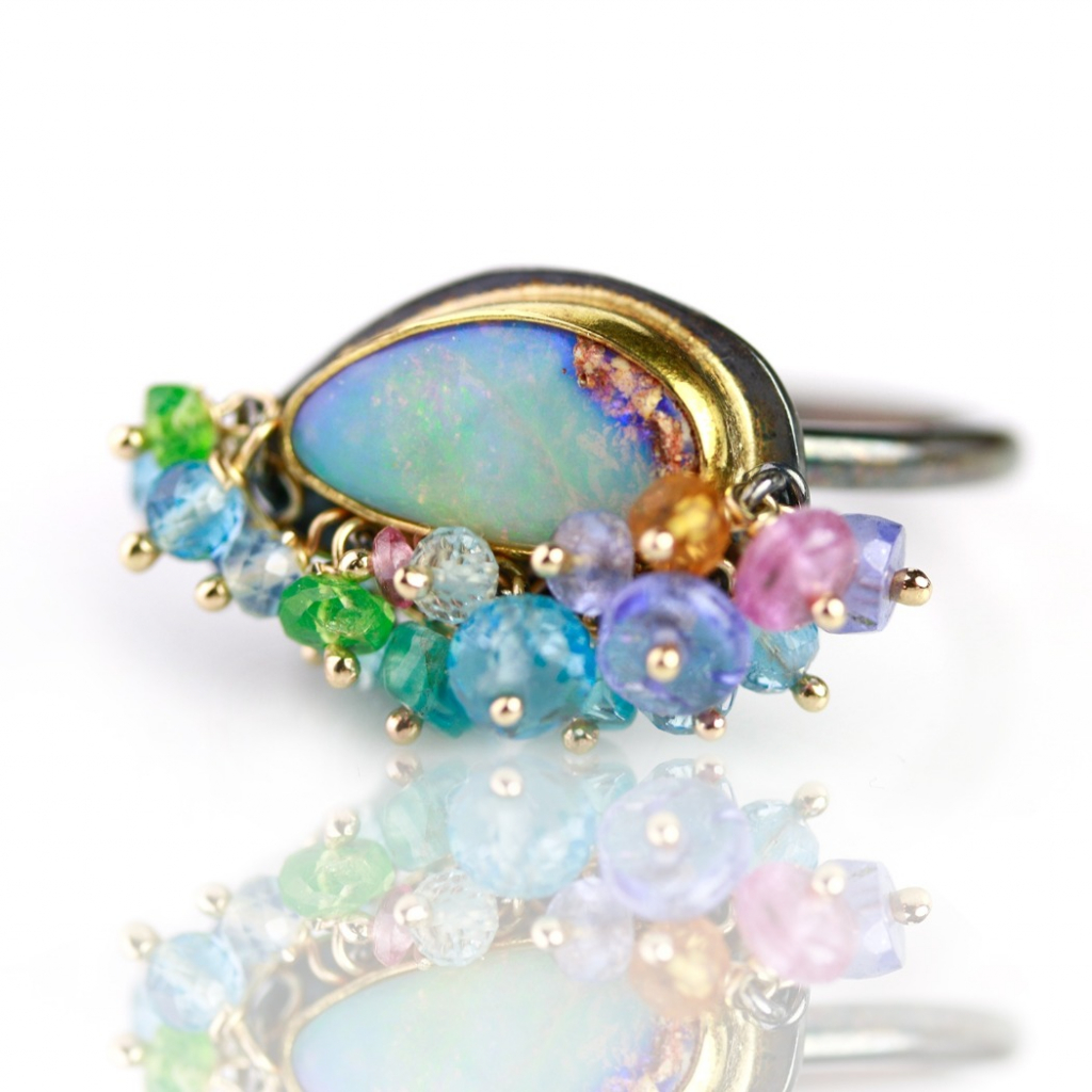 Ring in oxidized silver and 22k gold with Aqua Wood Fossil Boulder opal with mixed gemstones, $855; available online at Fuss Jewelry