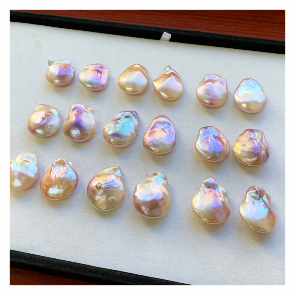 Flat baroque-shape freshwater pearls with pinkish-purplish overtones in sizes bigger than quarters, pairs range from $900 to $1,200 triple keystone (retail); email mail@elikopearl.com for purchase.
