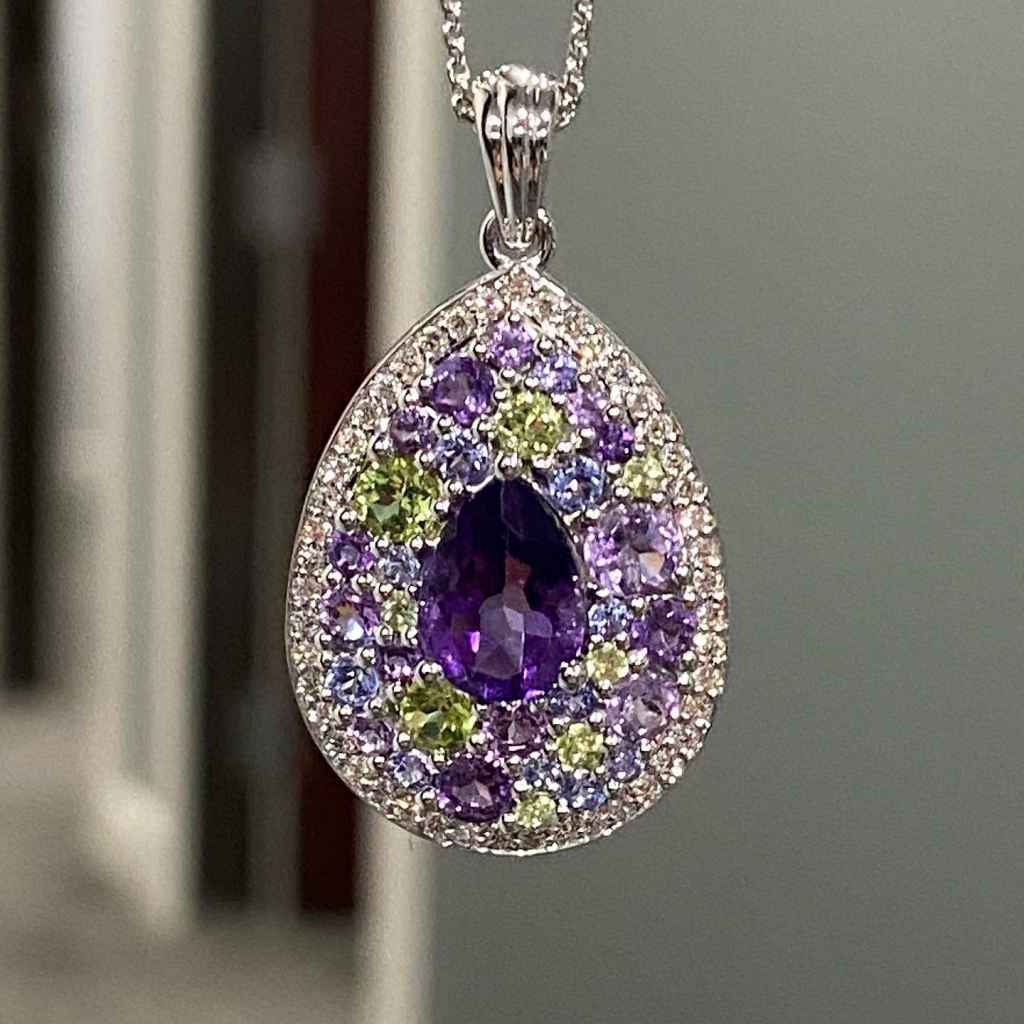 Custom-designed 14k white gold necklace with amethyst, tanzanite, and peridot surrounded by round brilliant-cut diamonds, $4,695; bid online for this piece by Indy Facets Private Jeweler