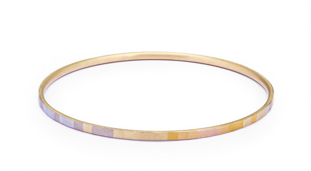 Rainbow Gold Bangle bracelet in 18k yellow gold with rainbow-hued facets in 18k and 24k gold and platinum, $3,750; available at Twist Online