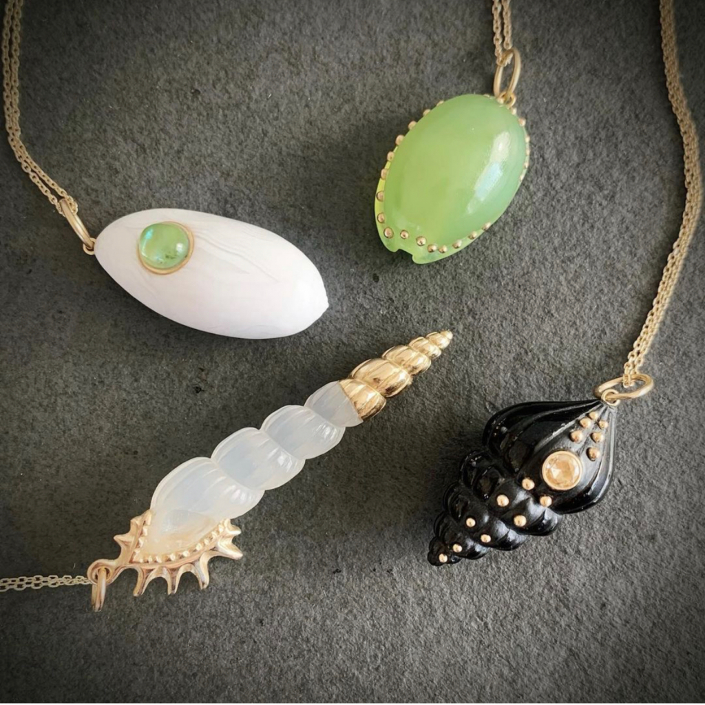 Cowrie shell with carved green Botswana agate and 14k gold, $2,285, and a carved milky chalcedony with 14k gold, $3,865. Charms only (no chain). The other shells are sold. Shop @sophiegardnerjewelry on Instagram.